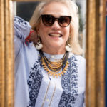 Ann Barish trying on an UNOde50 necklace